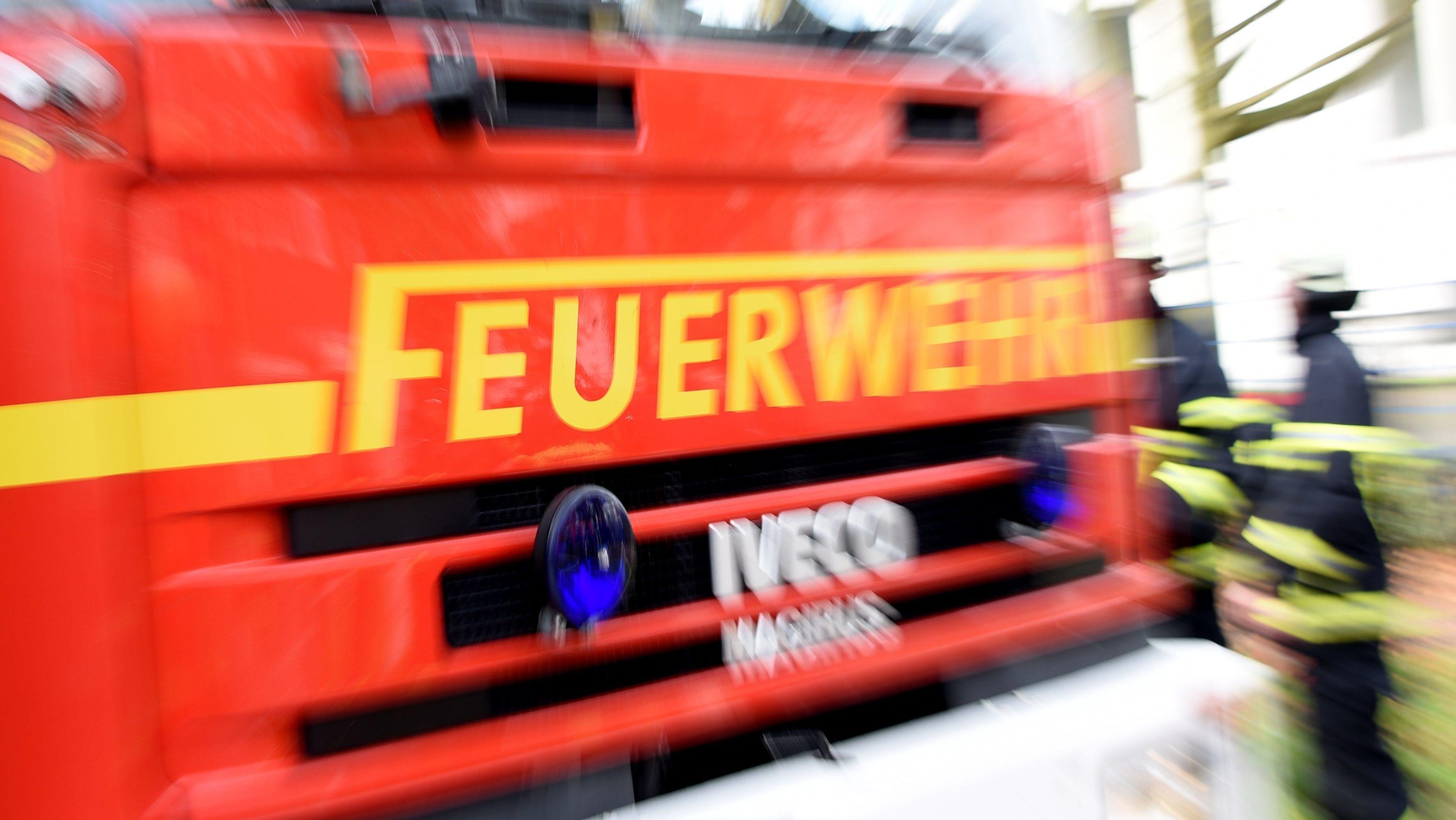 Ein Feuerwehrauto und Einsatzkräfte - Symbolbild