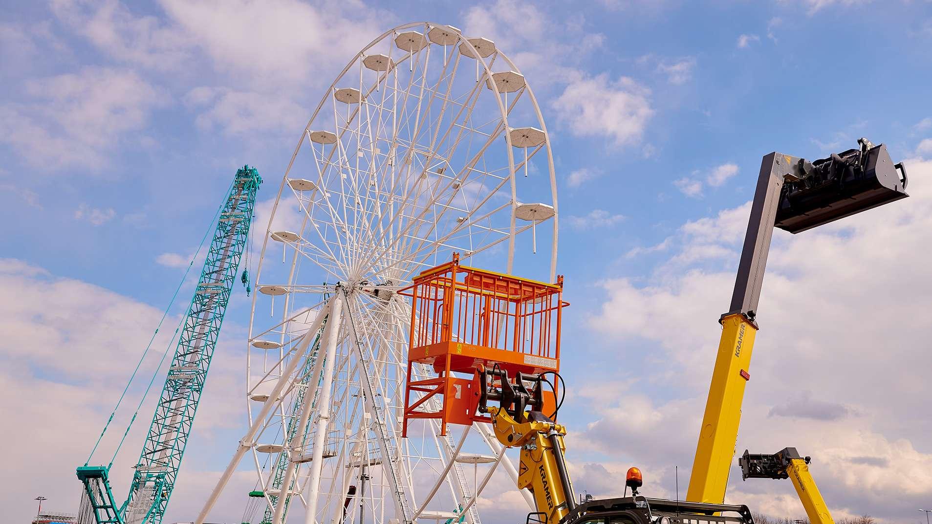 Auf dem Gelände der Messe München wird ein Riesenrad aufgebaut.