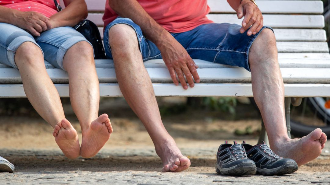 Barfuss sitzen Urlauber auf einer Bank