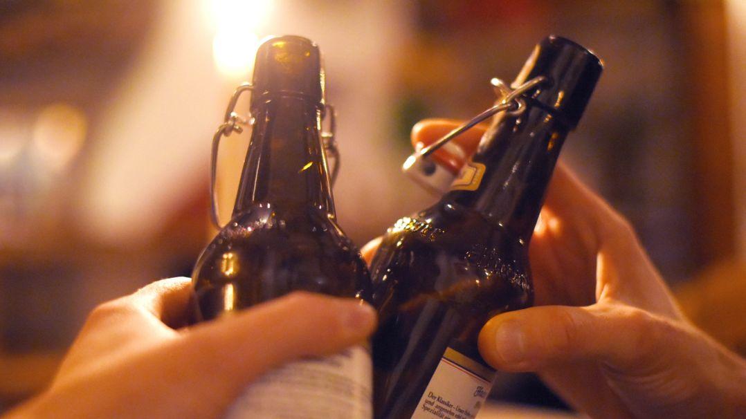 Zwei Menschen stoßen mit Bierflaschen an (Symbolbild).