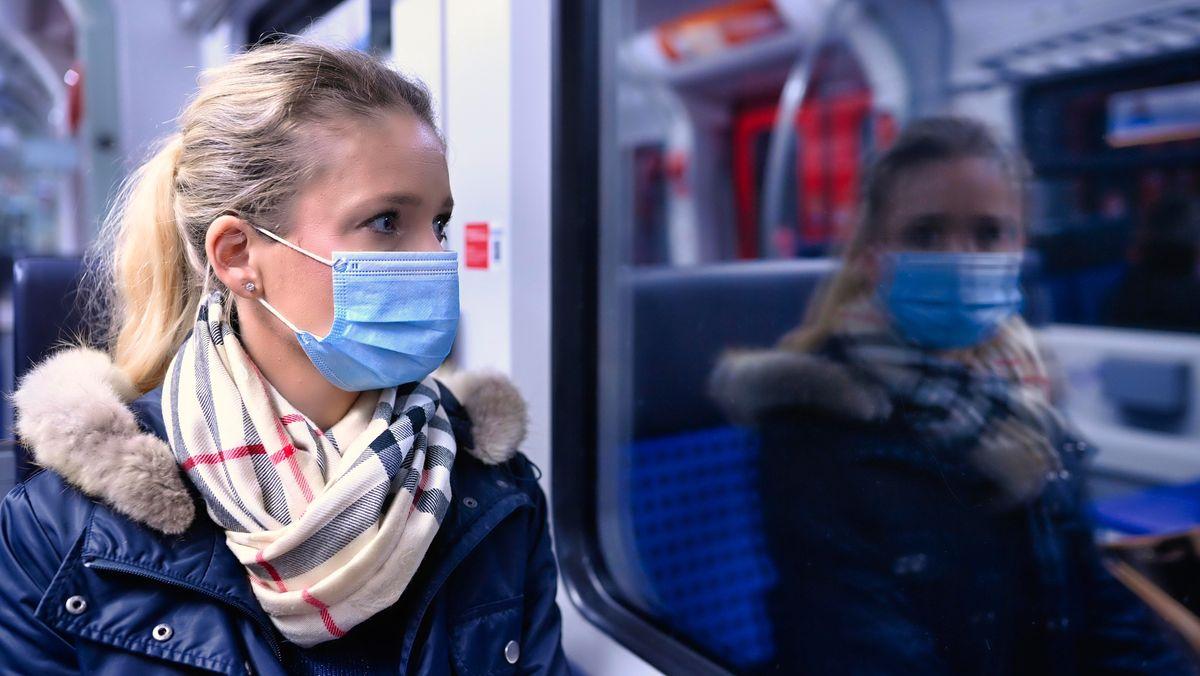 Frau sitzt in der S-Bahn und sieht nachdenklich nach draußen, sie spiegelt sich im Fenster.