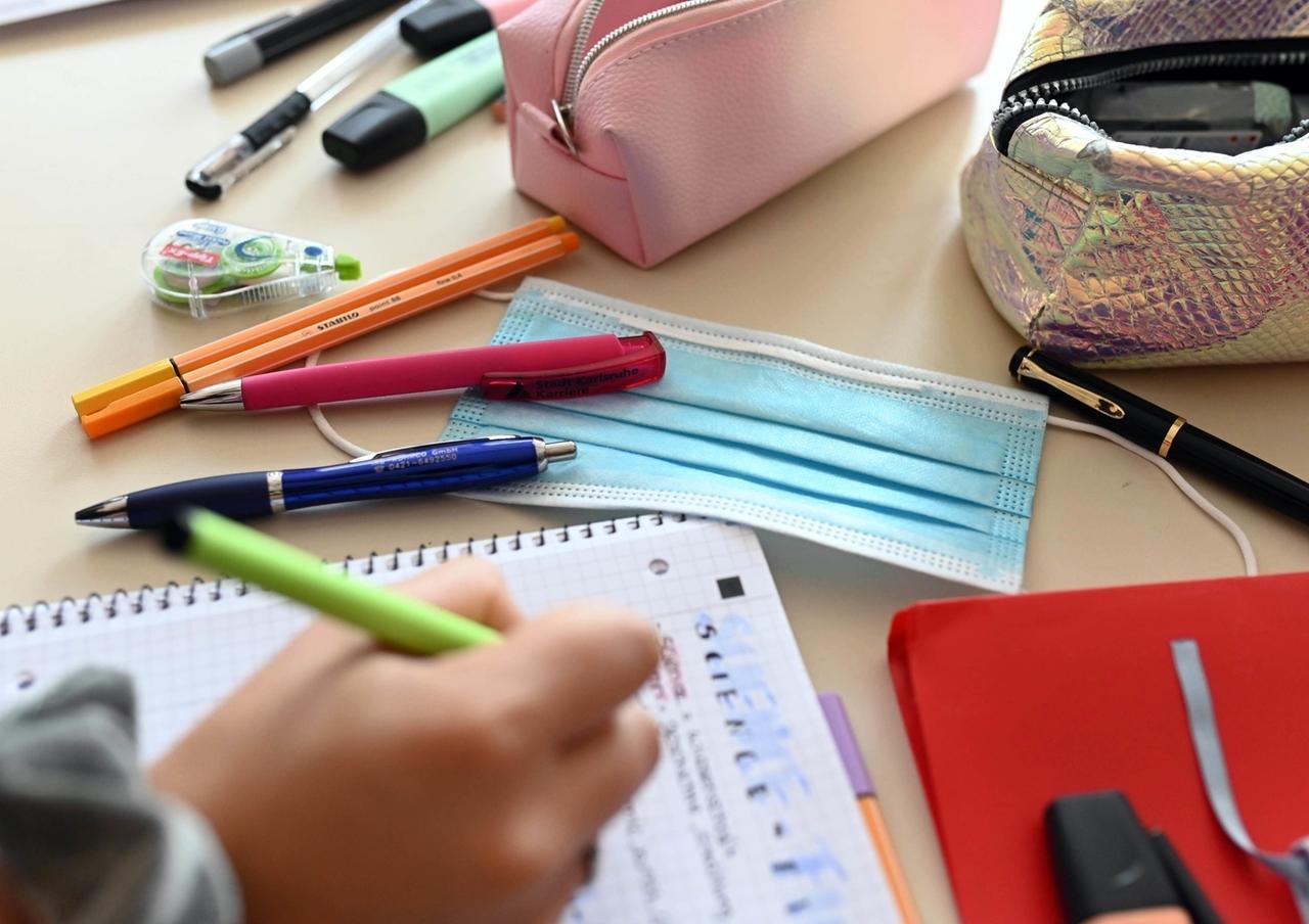 Schulstart unter Corona-Bedingungen: Eine Maske liegt zwischen Stiften auf einem Schreibtisch.