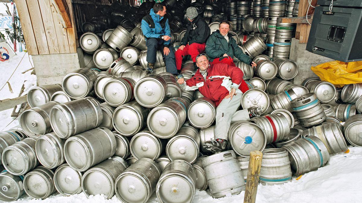 Fässer aus Aluminium türmen sich im Schnee, vier Männer in Schneeanzügen posieren darauf.