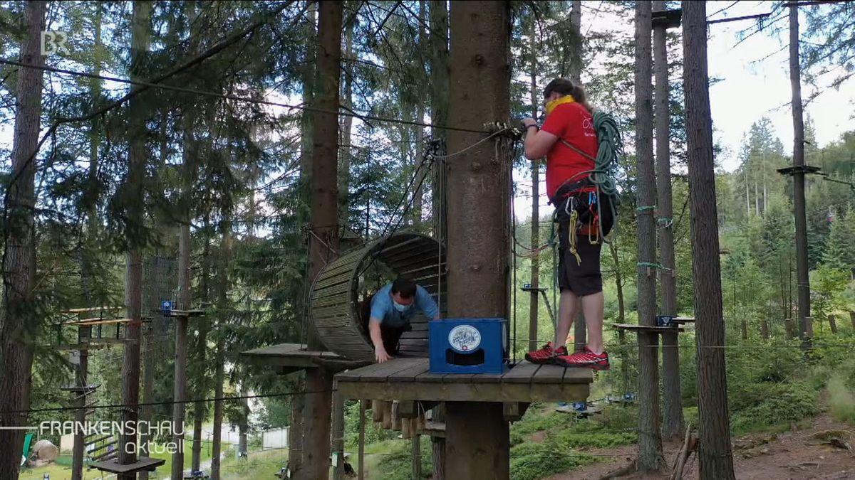 Ein Mann und eine Frau stehen auf einer Plattform, die an einem Baum angebracht ist, ein Seil zieht sich von einem Baum zum anderen.