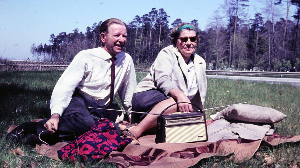 Ein Paar sitzt mit ihrem Radio beim Picknick auf der Wiese