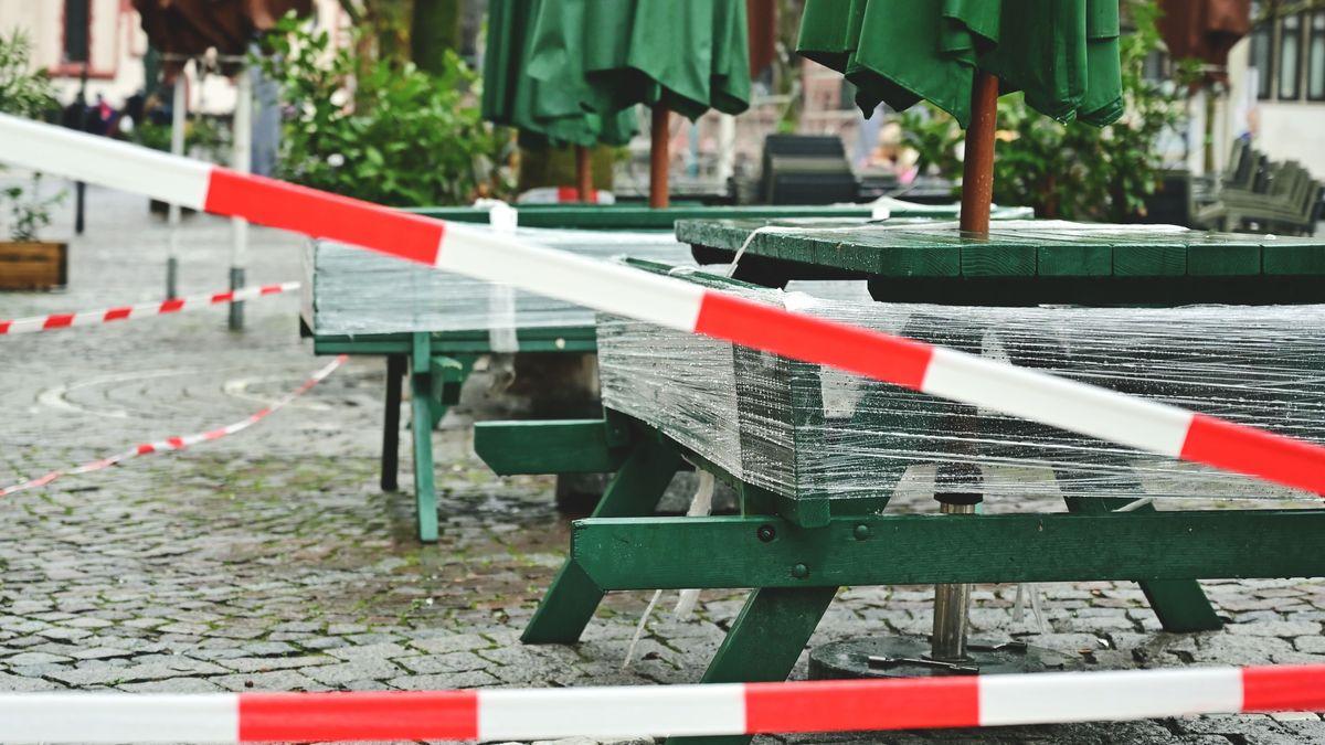 Tische einer Gaststätte im Außenbereich, davor rot-weißes Absperrband. Szene aus dem Lockdown in Deutschland, der wohl wieder verlängert wird