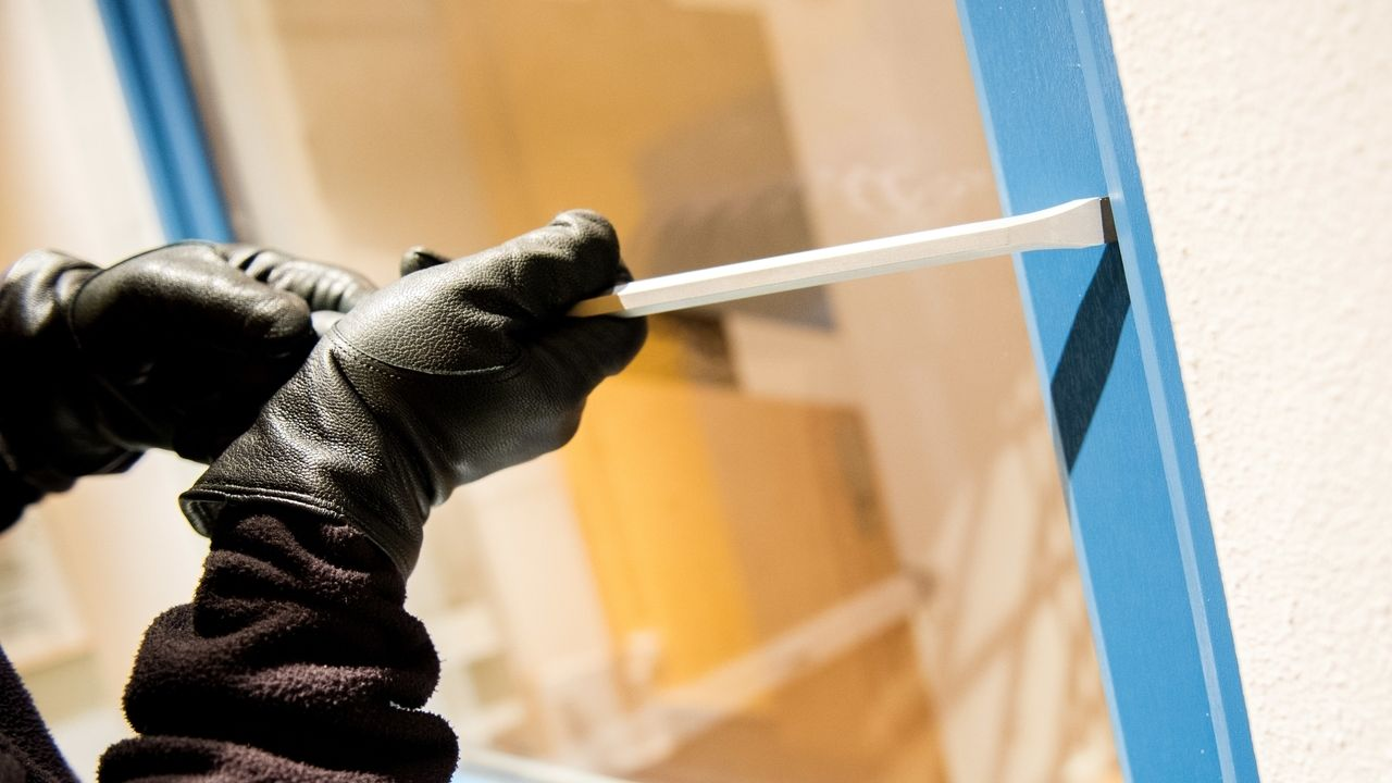 Mit schwarzen Handschuhen bekleidetet Hände versuchen mit einer Brechstange ein Fenster zu öffnen.