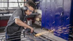 Ein Flüchtling aus Algerien arbeitet mit einer Flex an einem Metallgitter | Bild:BR/Philipp Kimmelzwinger