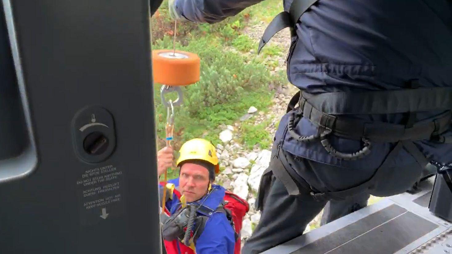 Blick aus dem Rettungshubschrauber wie ein Bergretter per Winde in den Helikopter gezogen wird
