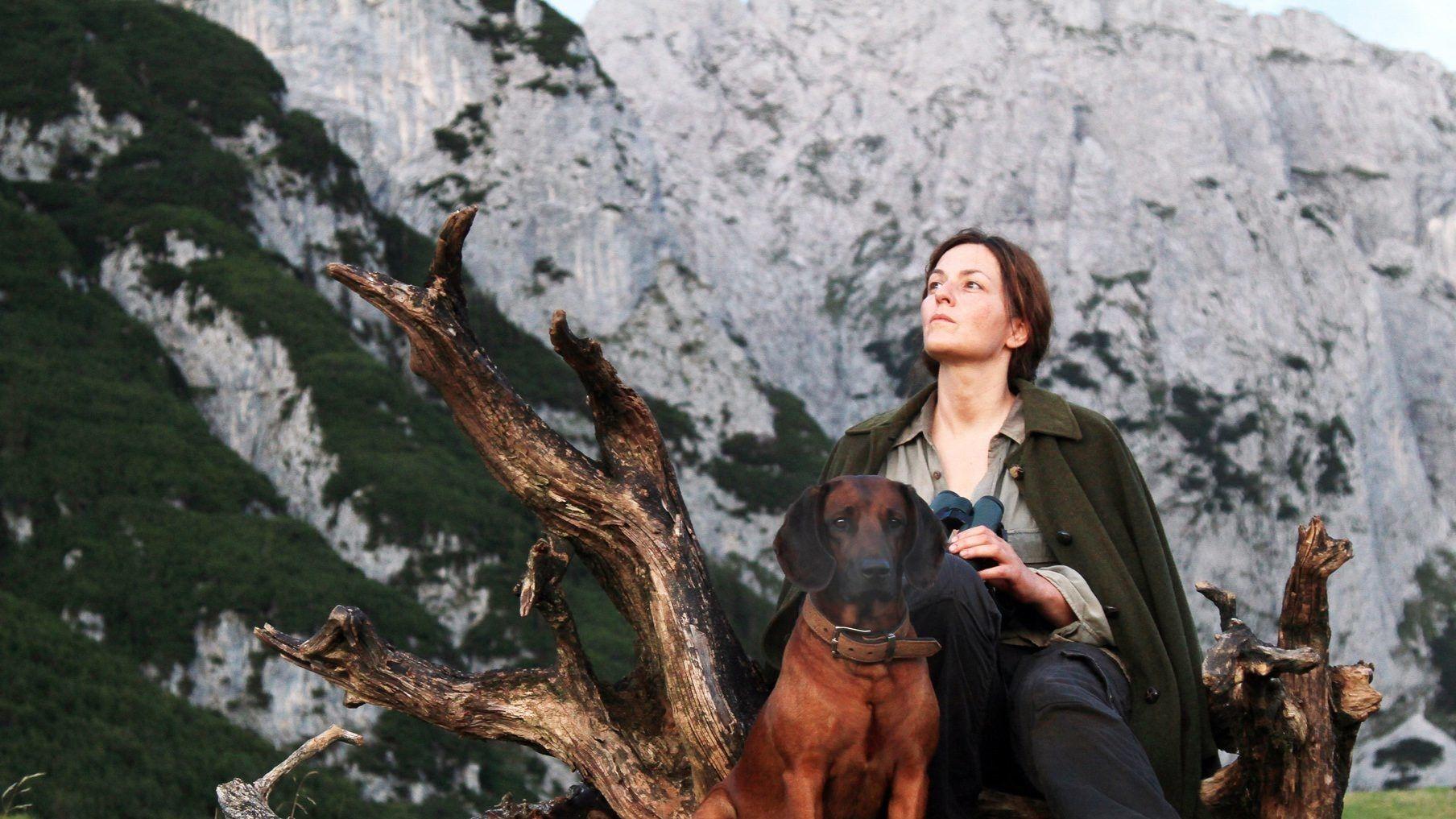 Der Filmausschnitt zeigt die Schauspielerin Martina Gedeck mit Hund, sitzend vor imposanter Bergkulisse.