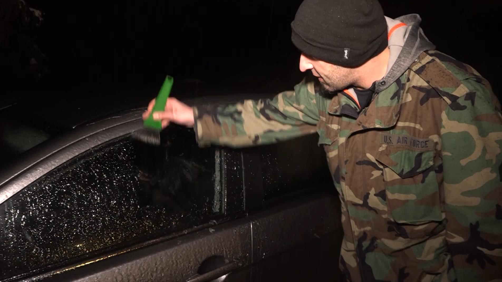Mann kratzt seine Autoscheiben vom Eis frei