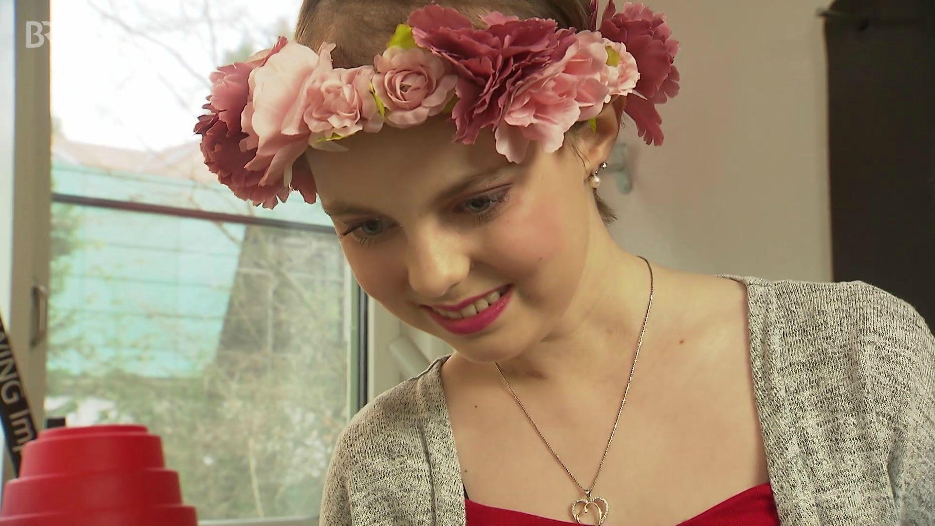 Die schön geschminkte Hannah Aurnhammer mit rosa Blumenkranz im Haar schaut sich Bilder in einer Kamera an