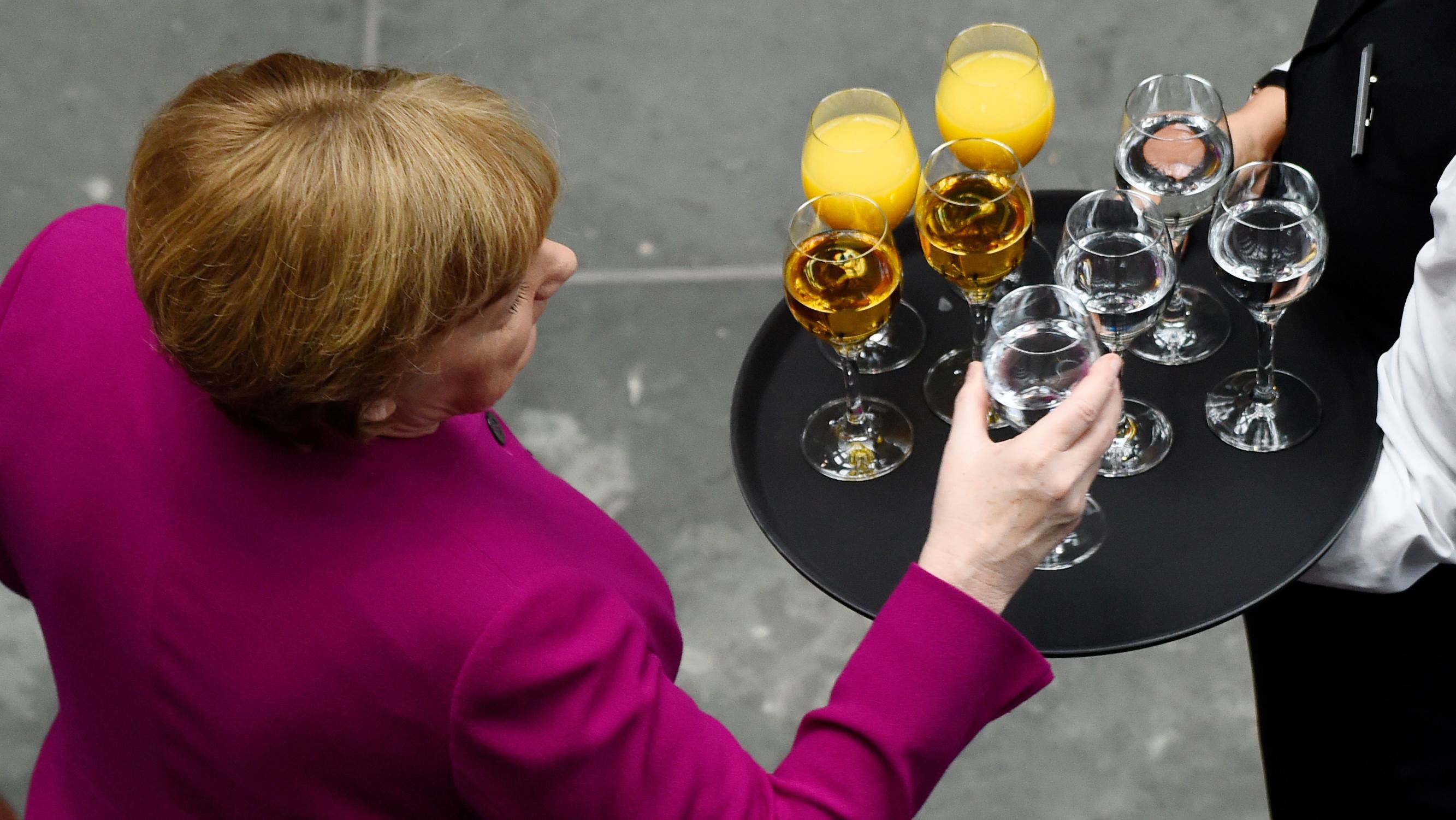 Angela Merkel greift zu einem Glas Wasser, das ihr auf einem Tablett mit Getränken gereicht wird.