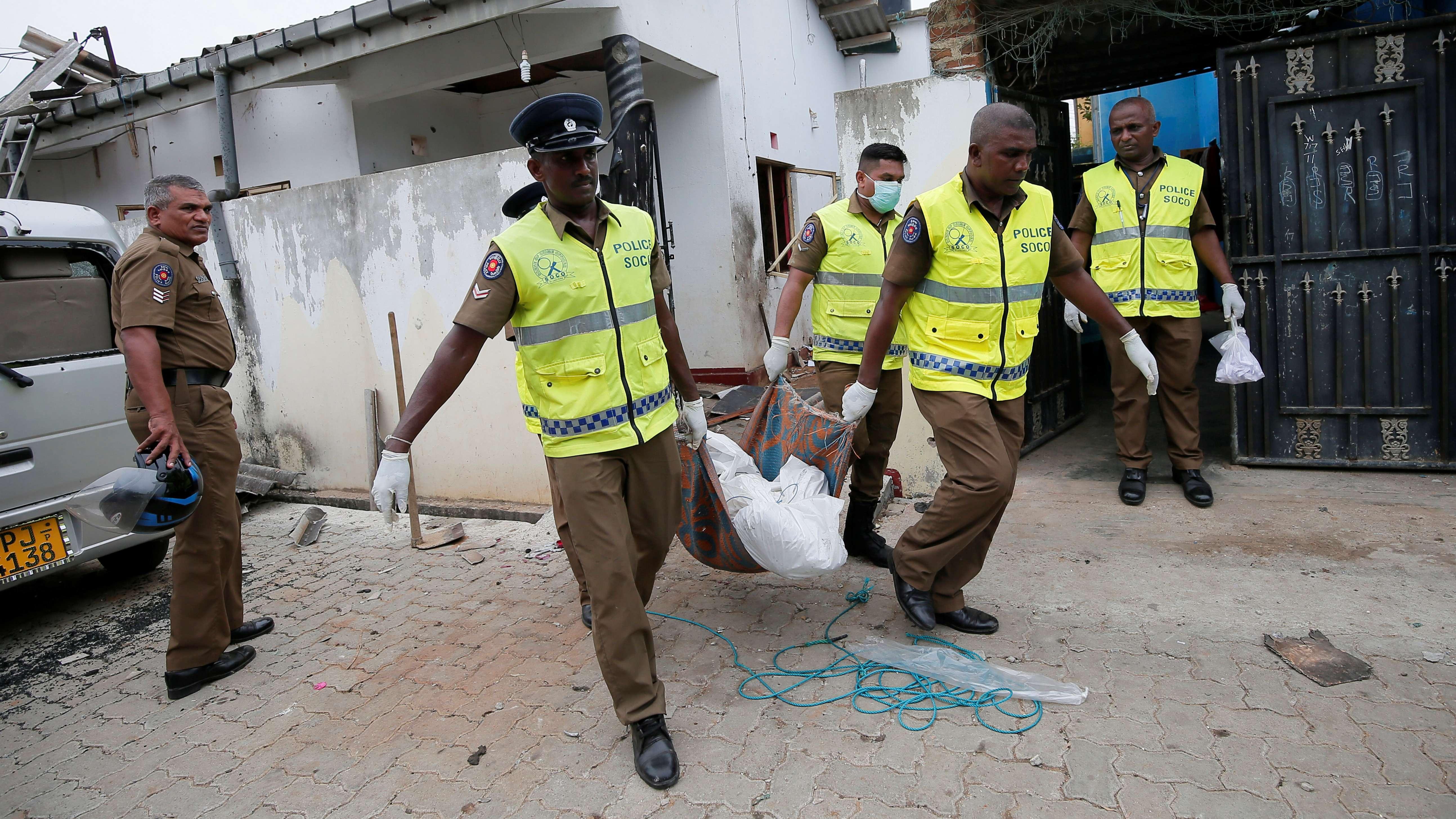 Polizisten tragen eine Leiche aus einem Haus in Kalmunai