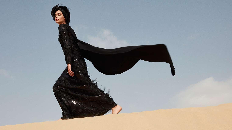 Frau in schwarzem Kleid läuft über Wüstensand.