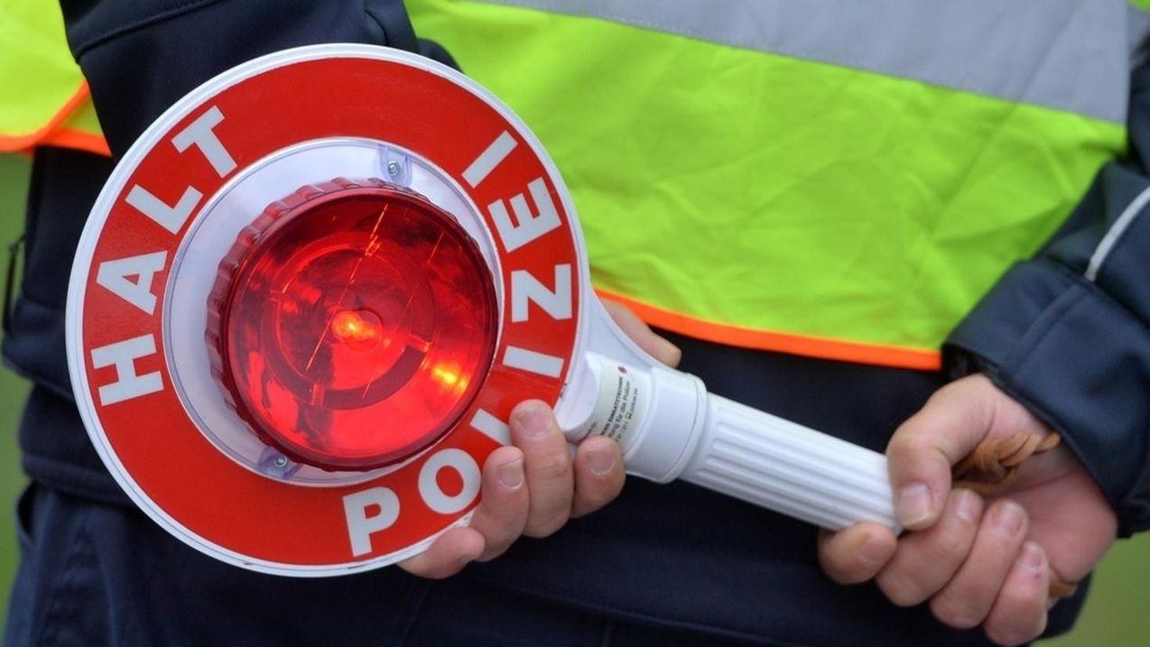 """Ein Polizeibeamter in gelber Warnweste hält eine Kelle mit der Aufschrift """"Halt, Polizei"""" in den Händen."""