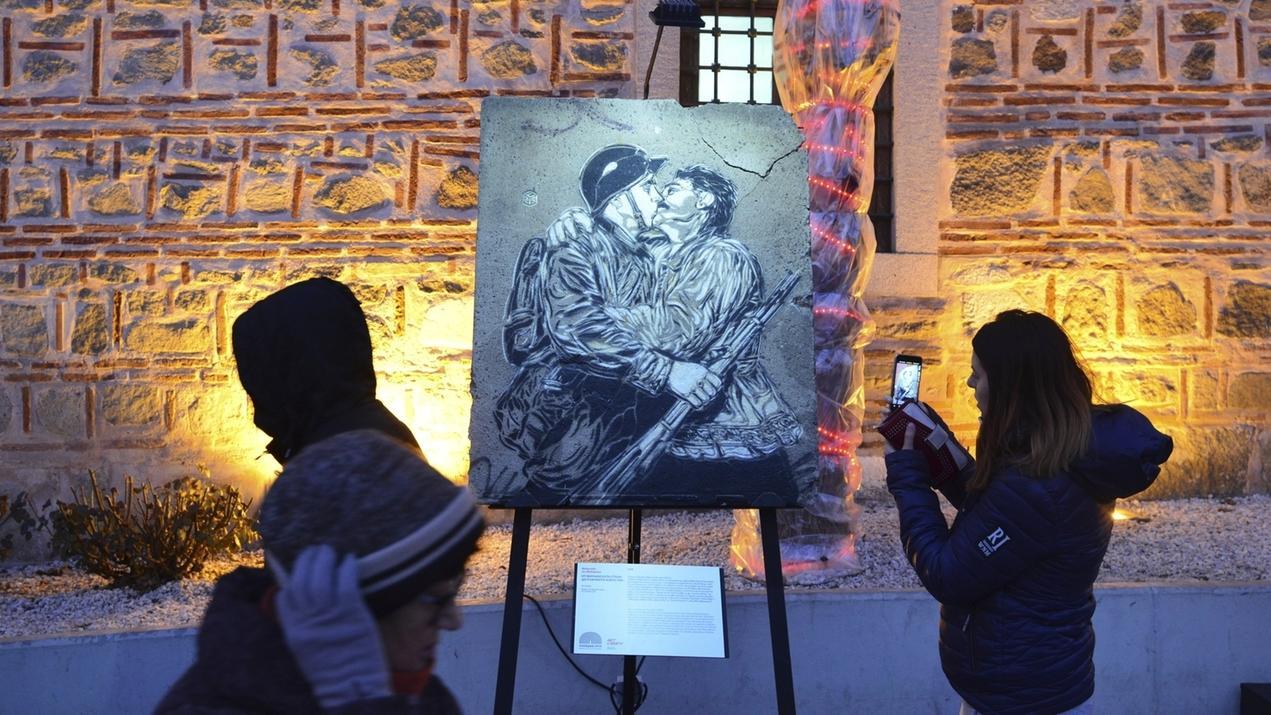 Eine Frau fotografiert ein Kunstwerk, das zu einer Ausstellung zum 30. Jubiläum des Berliner Mauerfalls gehört, und nun durch Europa tourt.