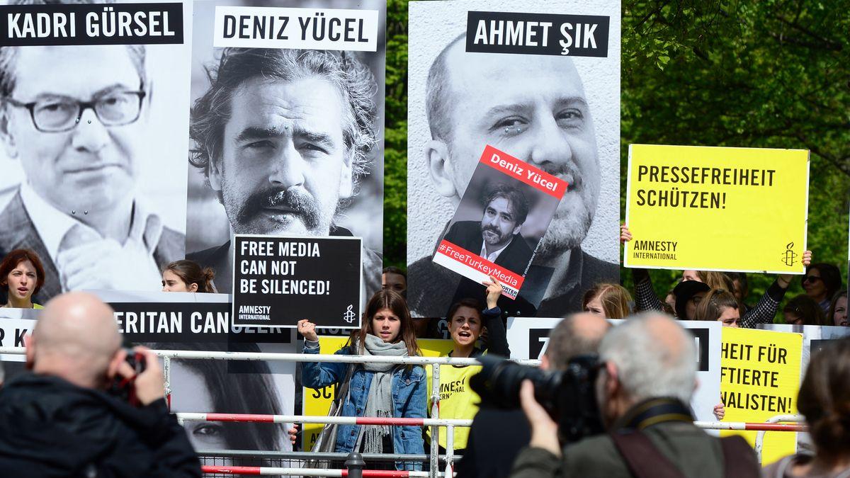 Schwarzweiß-Plakate mit drei Gefangenen: Kadri Gürsel, Deniz Yücel und Ahmet Sik und Demonstrant*innen