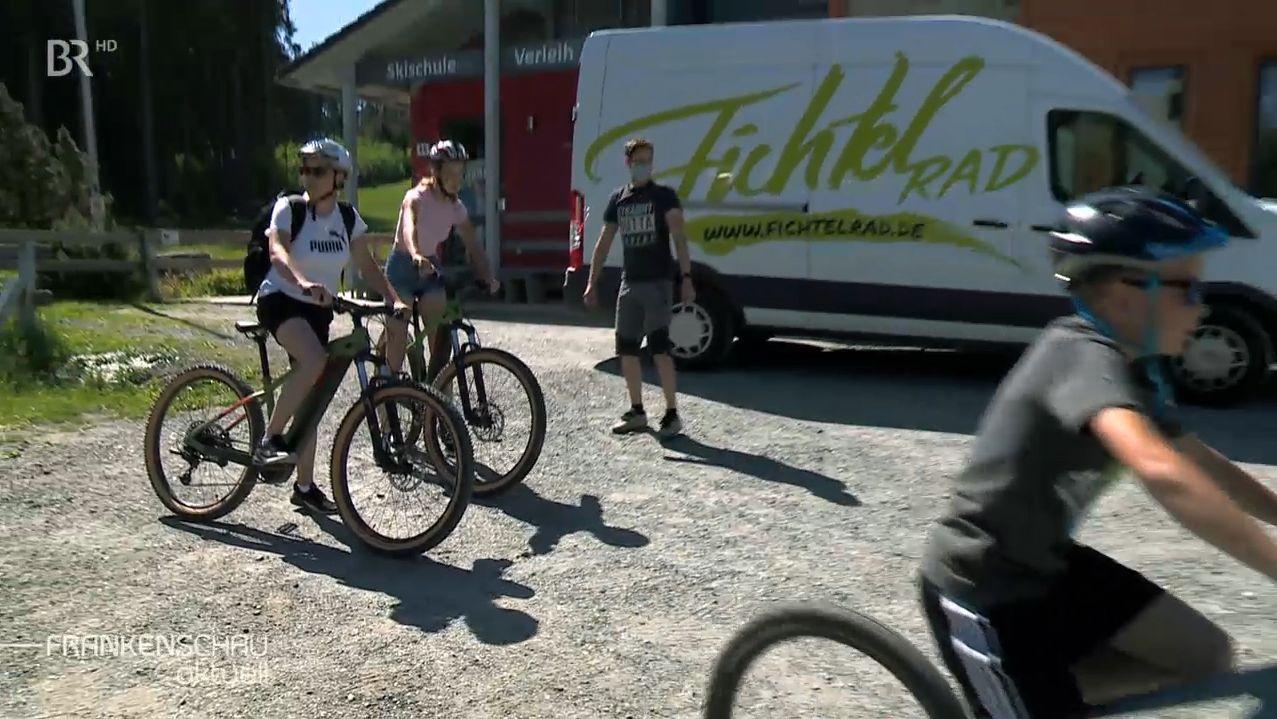 """Drei Radfahrer auf ihren Rädern warten vor einem weißen Transportfahrzeug mit der Aufschrift """"Fichtelrad""""."""