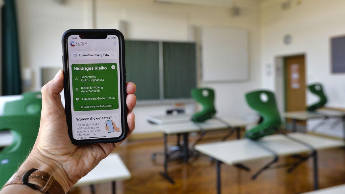 Hand hält Smartphone mit Corona Warn-App im Klassenzimmer