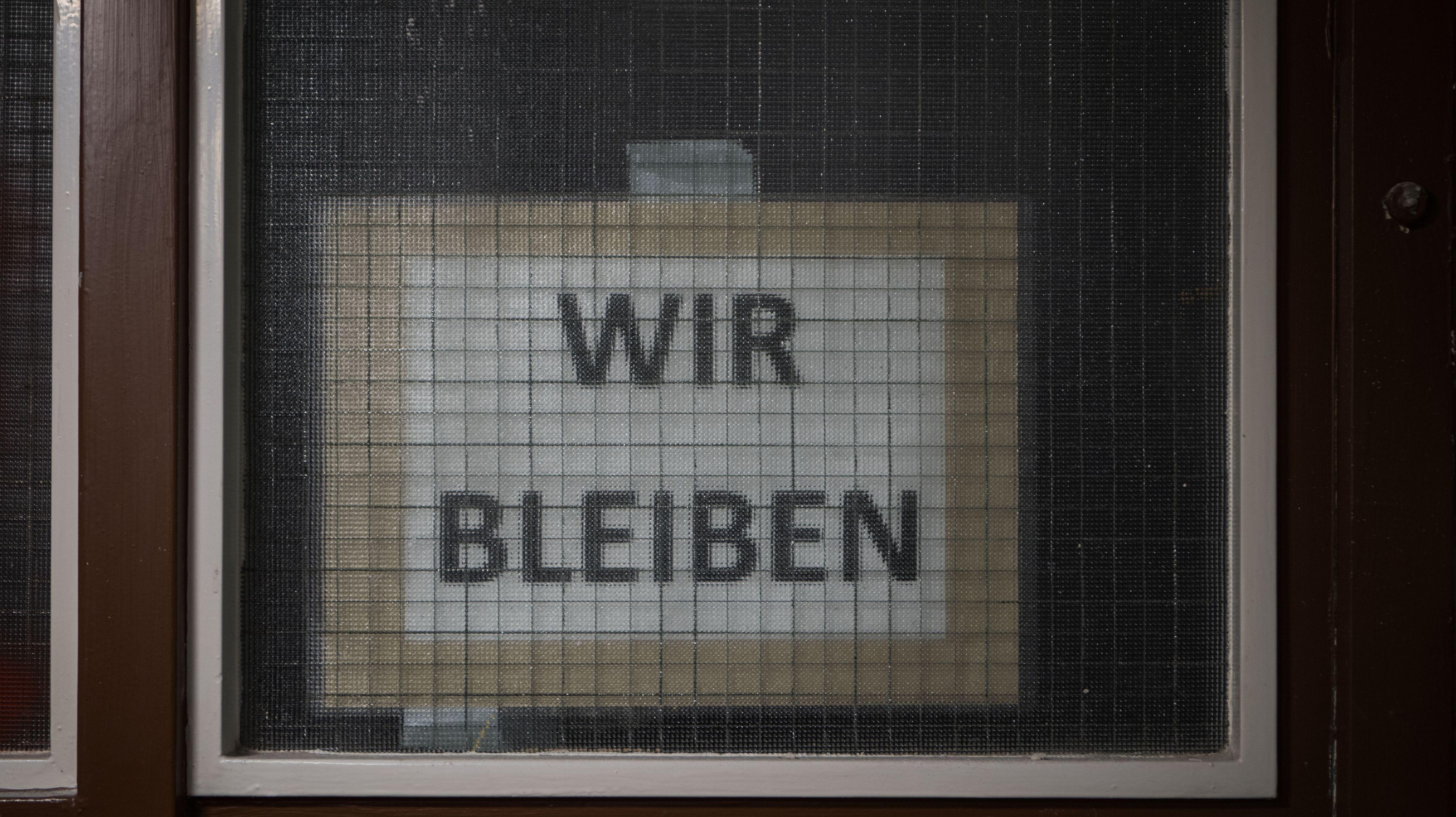 """Über der Wohnungseingangstüre hängt ein Zettel """"Wir Bleiben""""."""