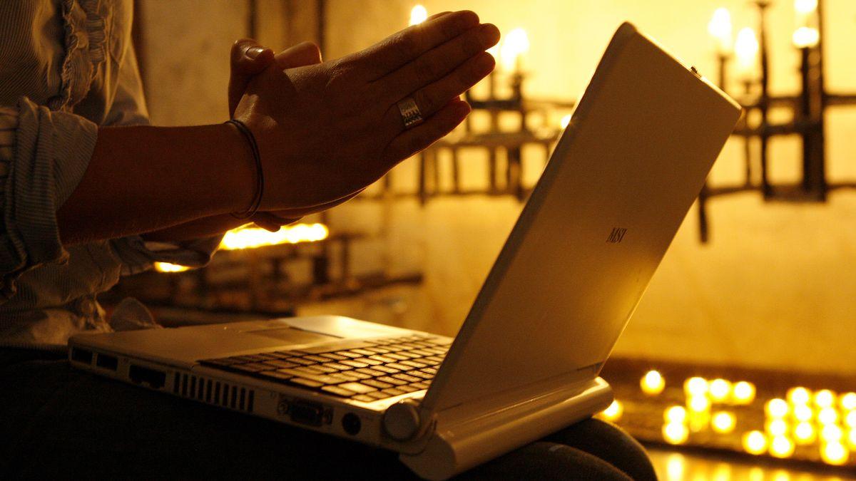 Betende Hände vor einem aufgeklappten Laptop (Symbolbild)