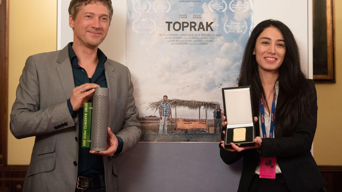 Die Regisseurin Sevgi Hirschhäuser und ihr Ehemann und Kameramann Chris Hirschhäuser halten einen Goldbarren und den Goldpreis in den Händen.