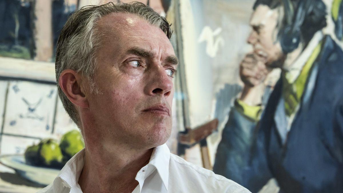 """Der Maler Neo Rauch, nach rechts aus dem Bild herausblickend, vor seinem Gemälde """"Die Erwartung"""""""