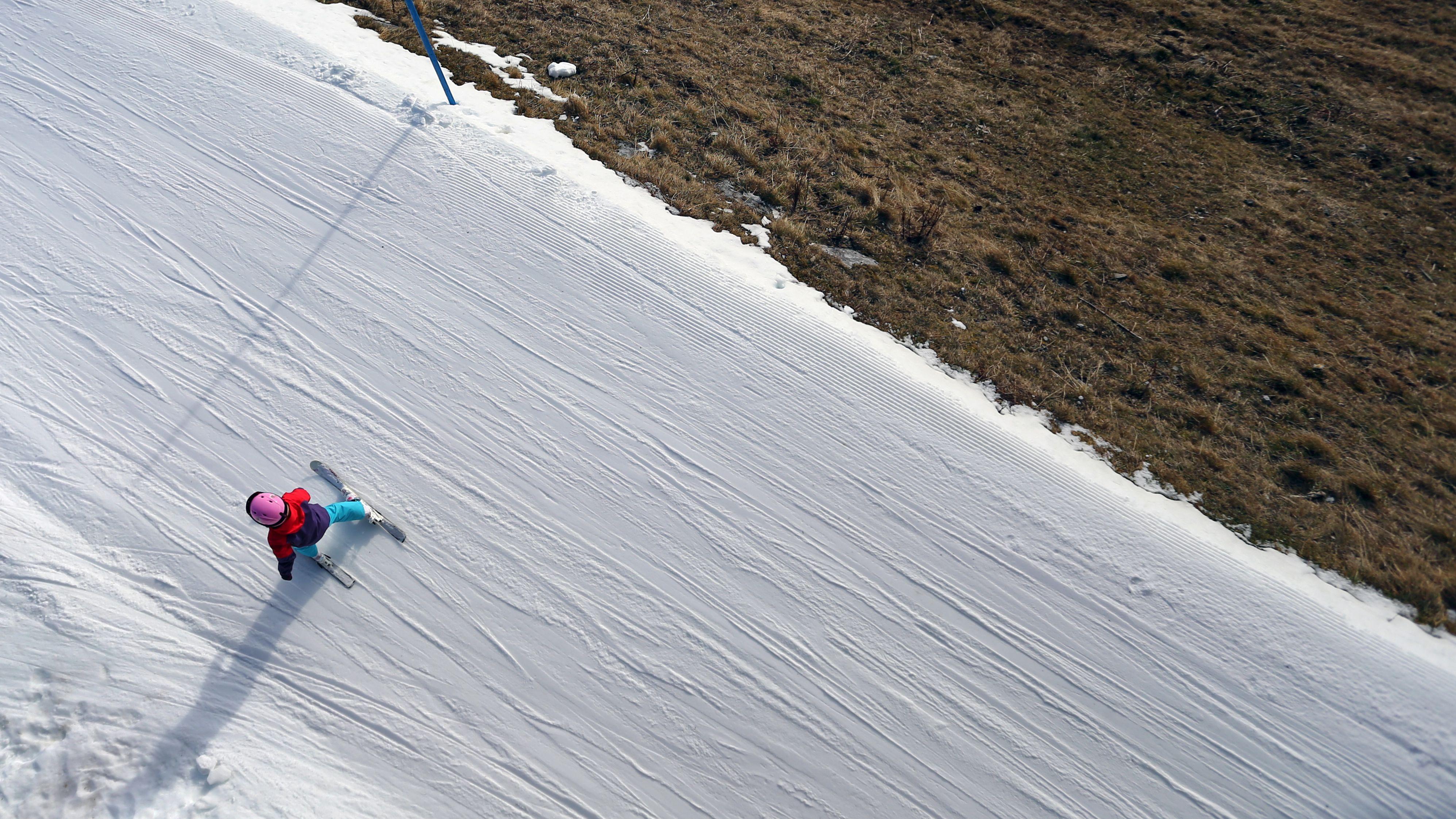 Kind fährt auf Streifen Schnee, neben der Piste Gras