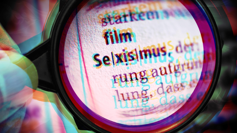 """Lupe zeigt das Wort """"Sexismus"""" in einem Lexikon"""