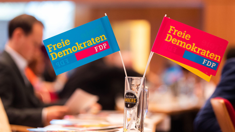 Fähnchen mit dem Logo der FDP stehen beim bayerischen Landesparteitag der Partei auf einem Tisch.