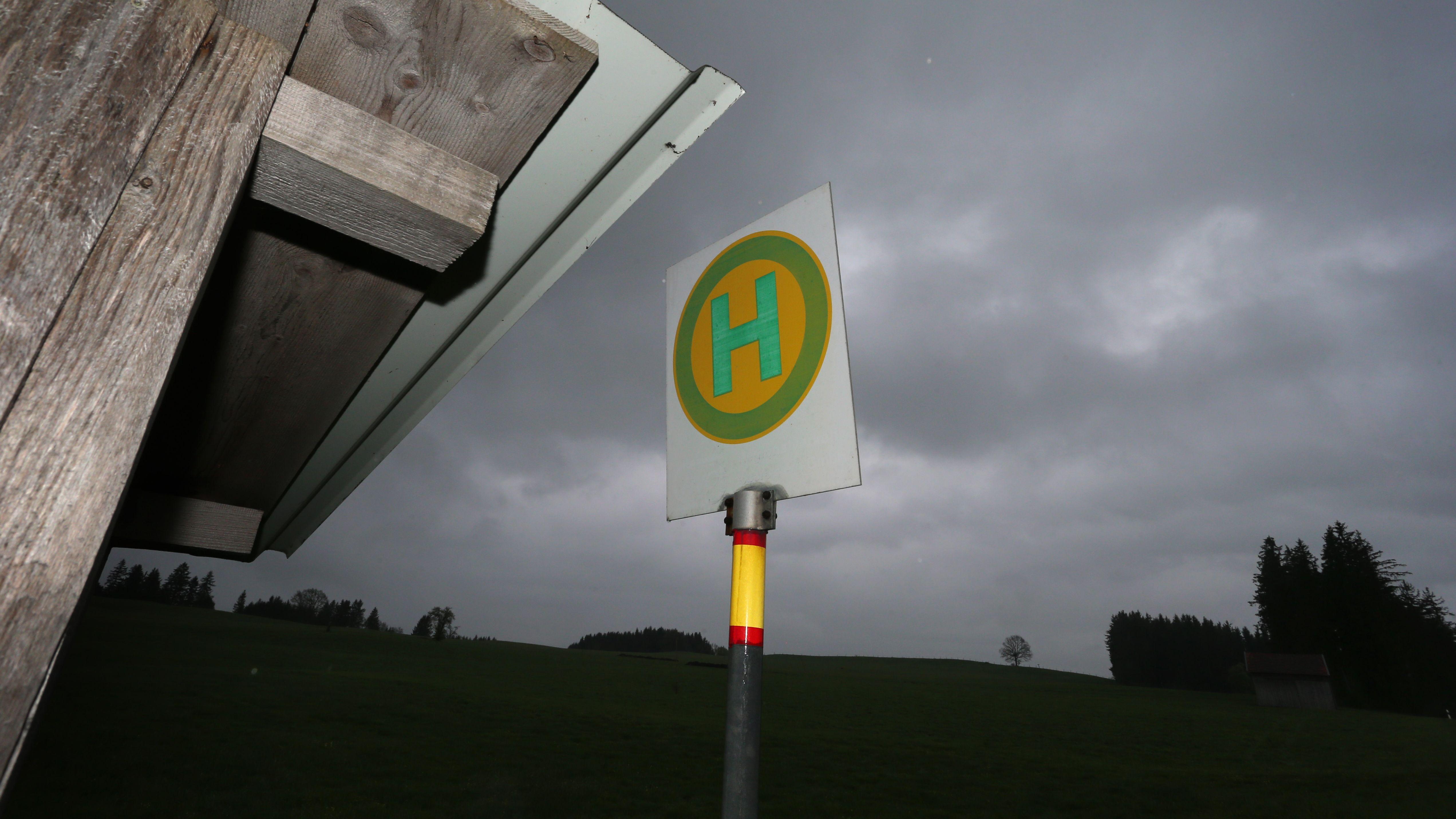 Eine Haltestellenzeichen ragt an einer kleinen Bushaltestelle in den dunklen Himmel