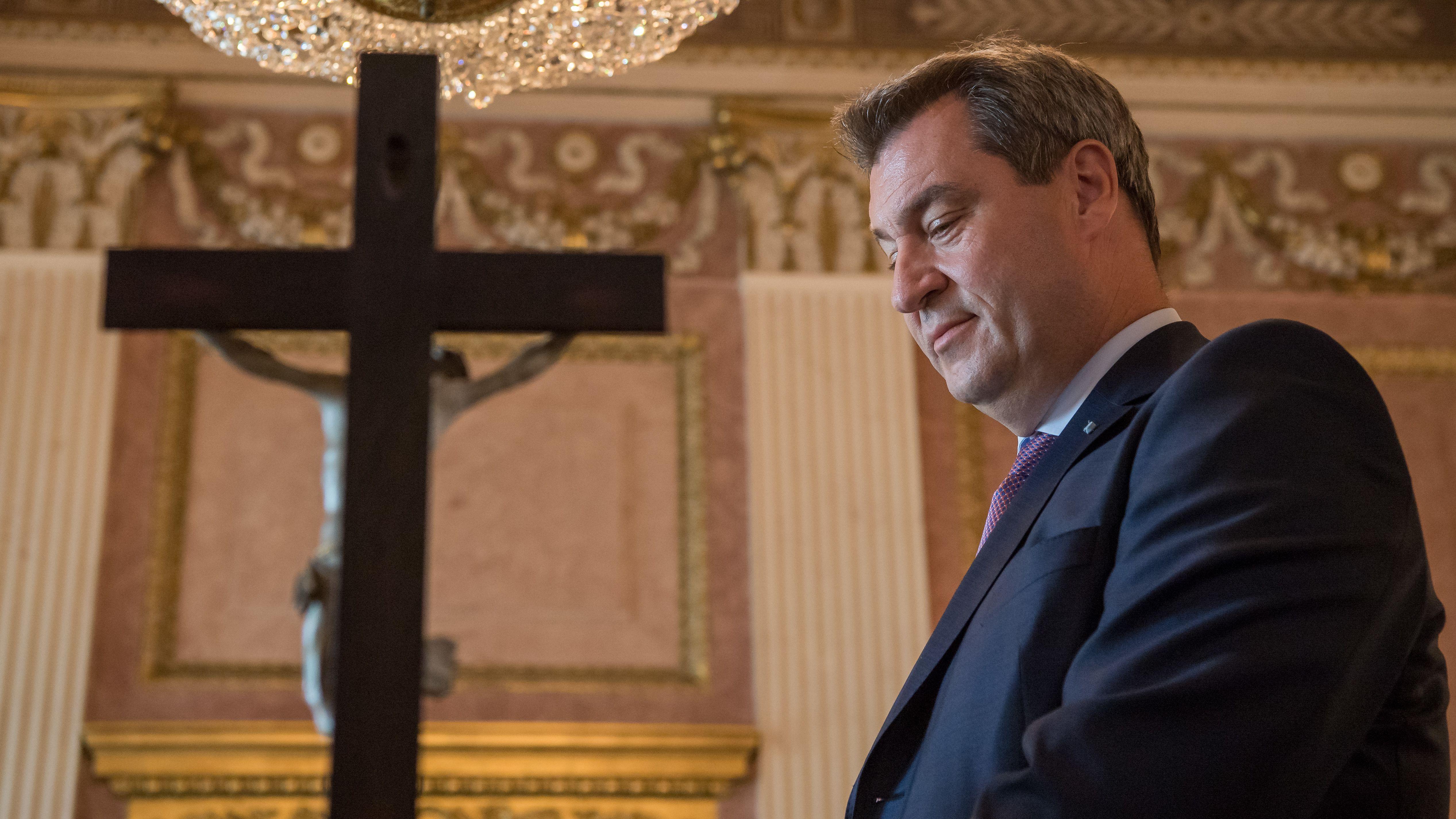 Der bayerische Ministerpräsident Söder neben einem Kruzifix
