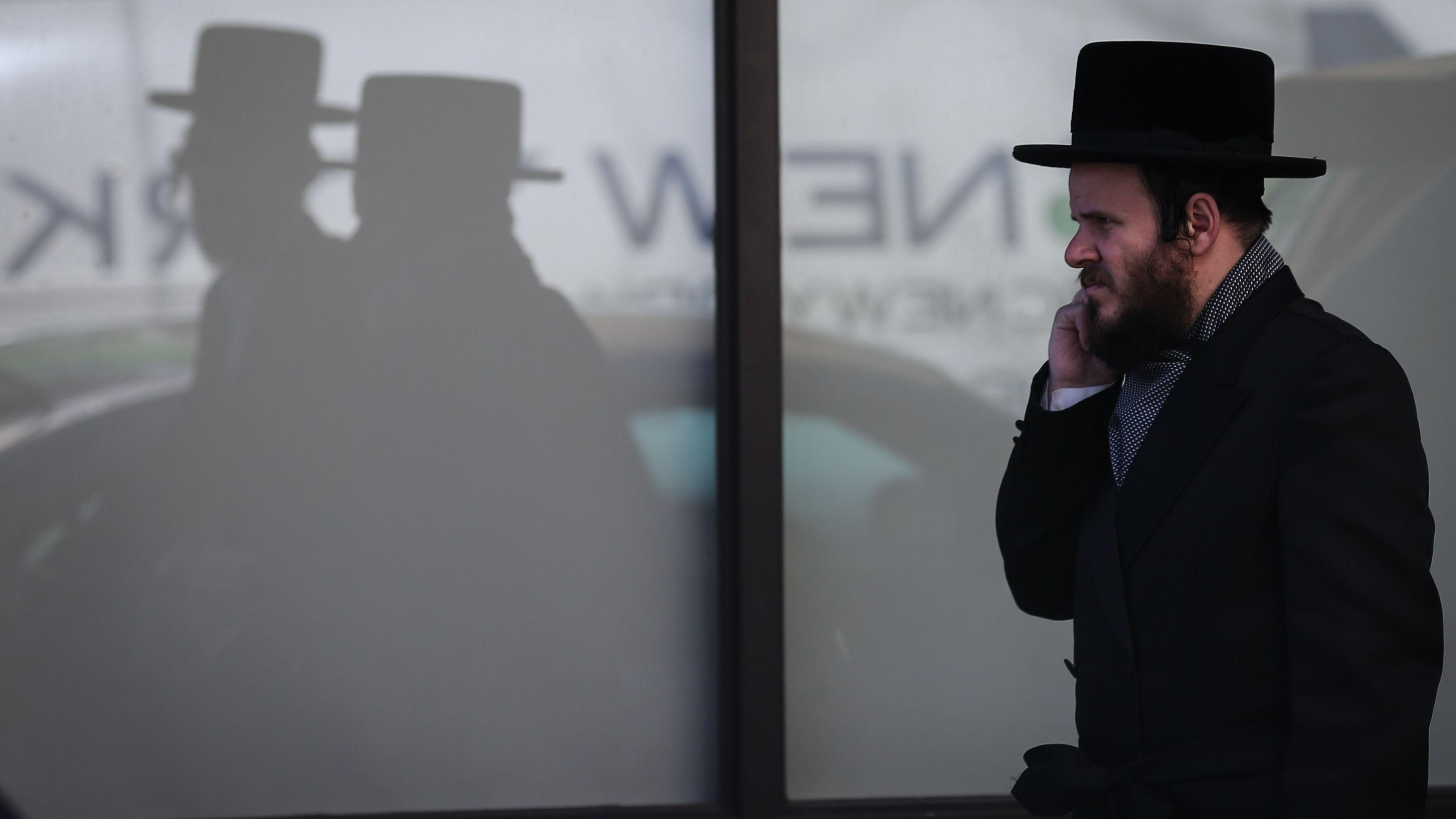 Ein jüdischer Mann geht telefonierend eine Straße in New York entlang
