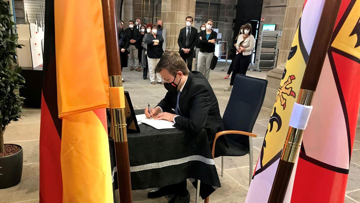 Oberbürgermeister Marcus König trägt sich ins Kondolenzbuch für Dani Karavan ein