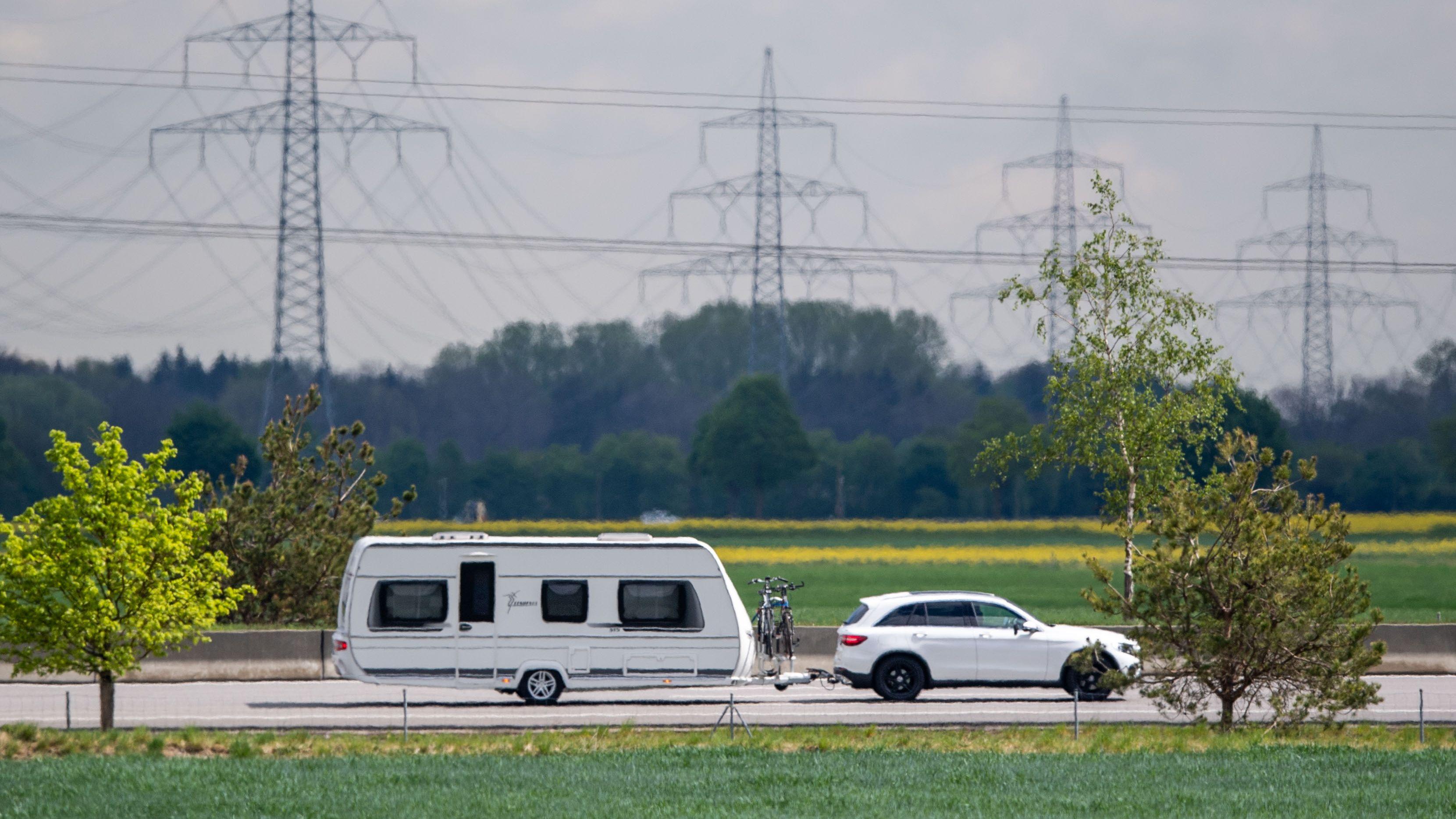 Symbolbild: Ein Auto mit Wohnwagen fährt auf der A8 bei Garching vor Strommasten entlang.