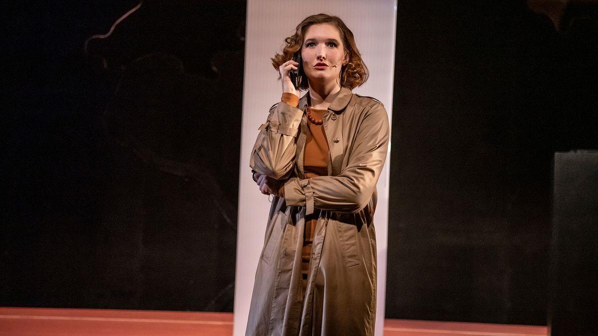 Frau im Trenchcoat mit Handy
