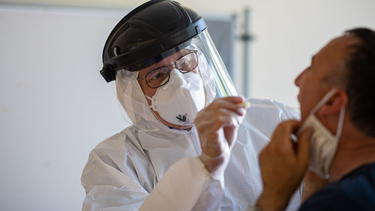 Ein Arzt macht einen Abstrich bei einem Patienten