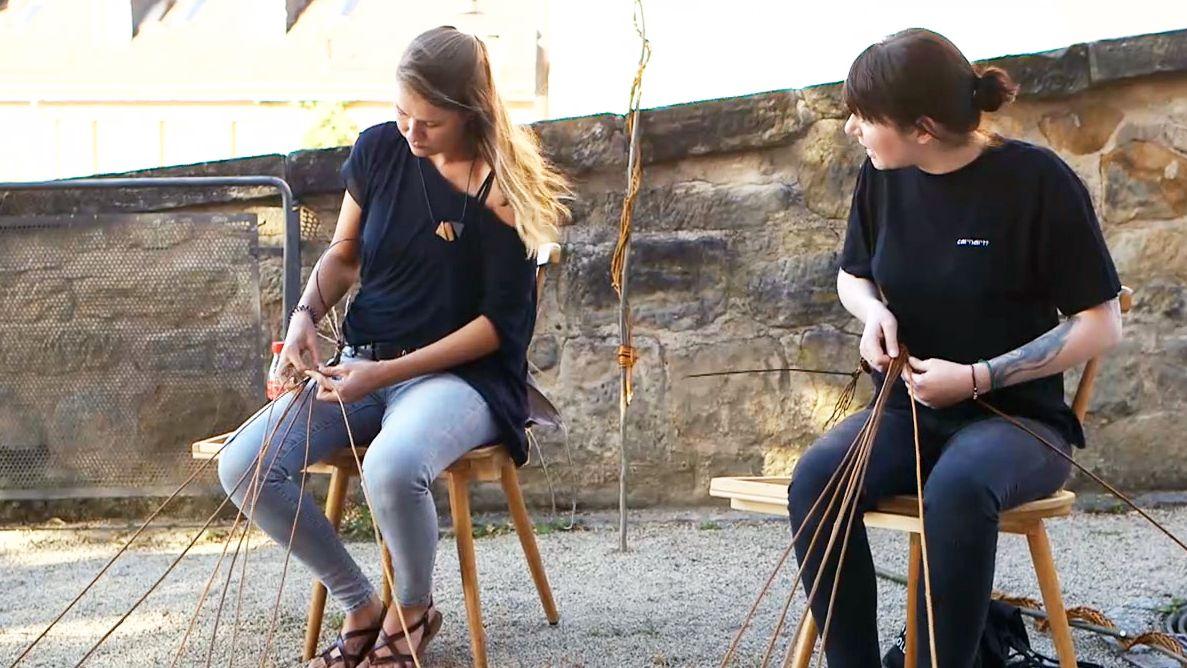 Zwei Frauen in Jeans und dunklen T-Shirts sitzen auf Holzstühlen und flechten.