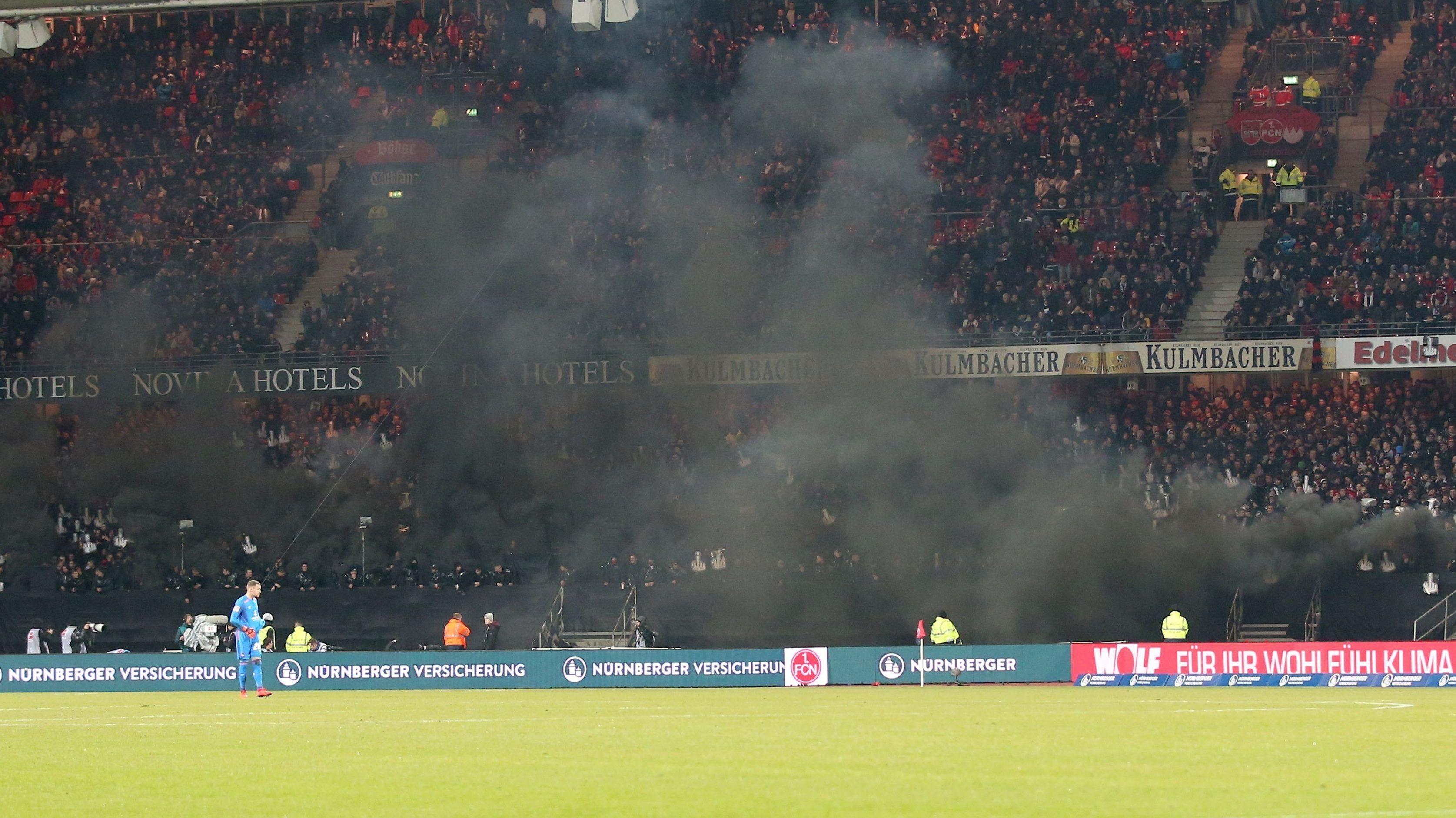 Schwarze Rauchschwaden ziehen beim Spiel des 1. FC Nürnberg gegen Borussia Dortmund über das Spielfeld im Frankenstadion.