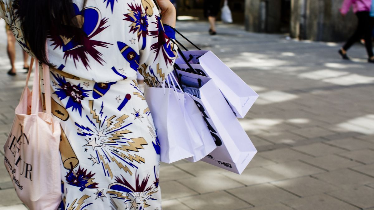 Eine junge Frau mit Einkaufstüten in der Münchner Fußgängerzone