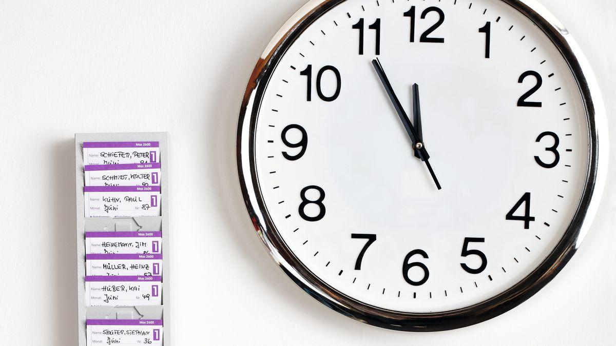 Neben einer großen Wanduhr hängt ein Kasten mit Zeiterfassungskarten.