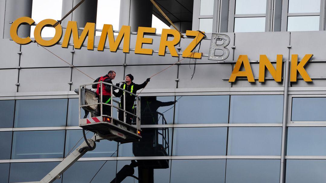 Arbeiter demontieren den Schriftzug an einer Commerzbankfiliale