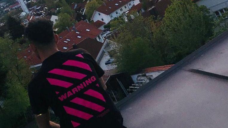 Parwiz, ein Geflüchteter, sitzt auf einem Hausdach. Er ist nur von hinten zu sehen, weil er anonym bleiben möchte.
