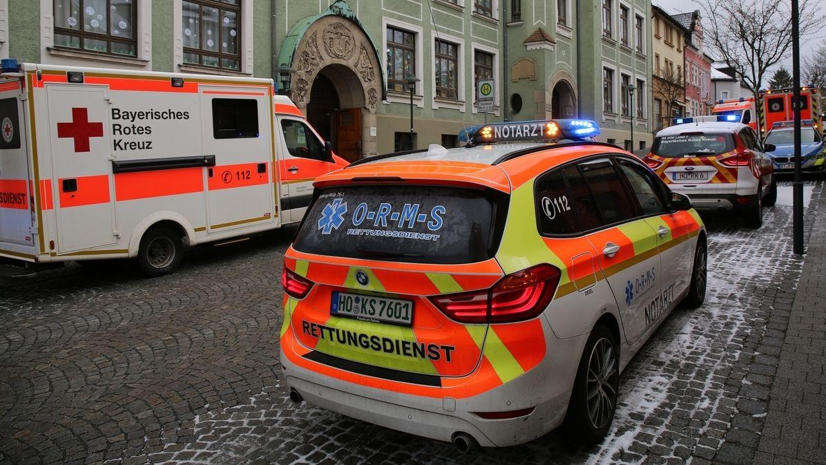 Rettungsfahrzeuge stehen vor einer Schule auf der Straße.
