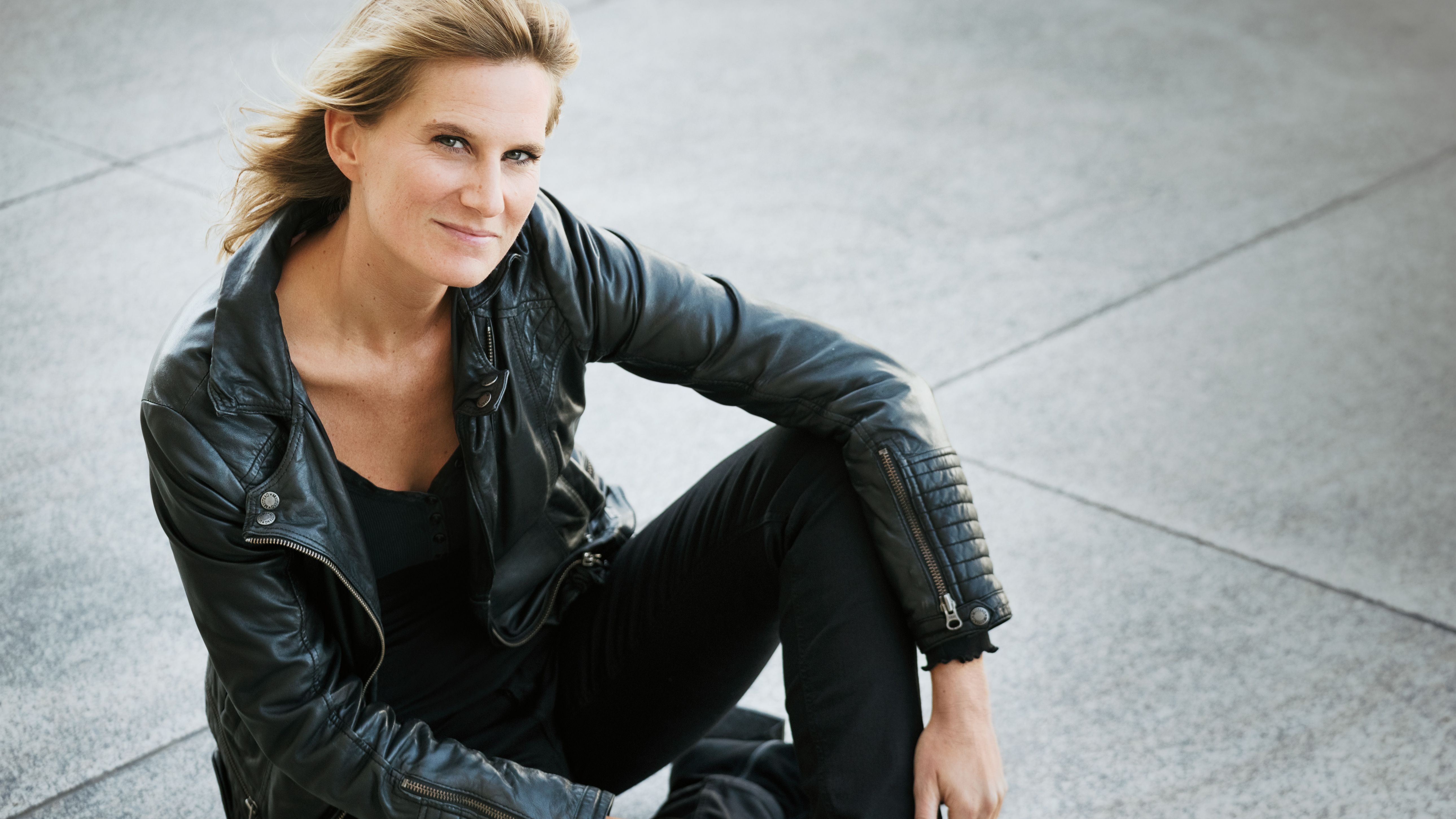 Lucy van Kuhl mit Liedermacher-Perfektion: Die Kölnerin sitzt am Boden, in schwarzer Laderjacke und Jeans