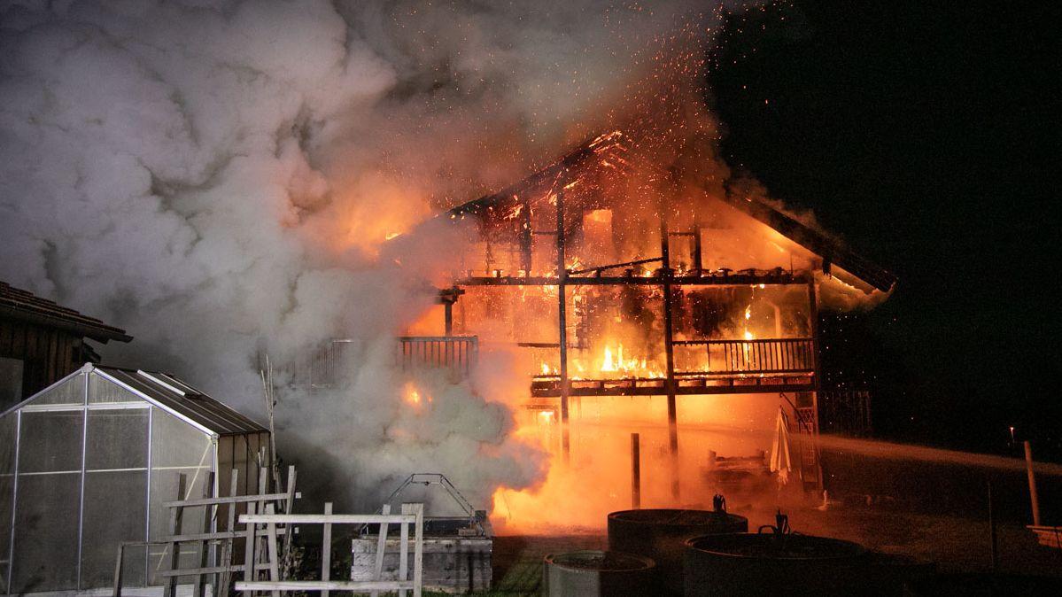 Bick auf das Haus von vorn, die komplette Fassade steht in Flammen. Holz aus Dach und Balkon bricht herab. Links im Bild dichte graue Rauchschwaden.