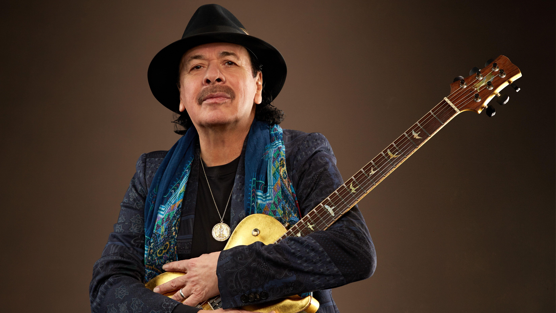 Carlos Santana hält seine braun-goldene Gitarre im Arm (Pressefoto 2019)