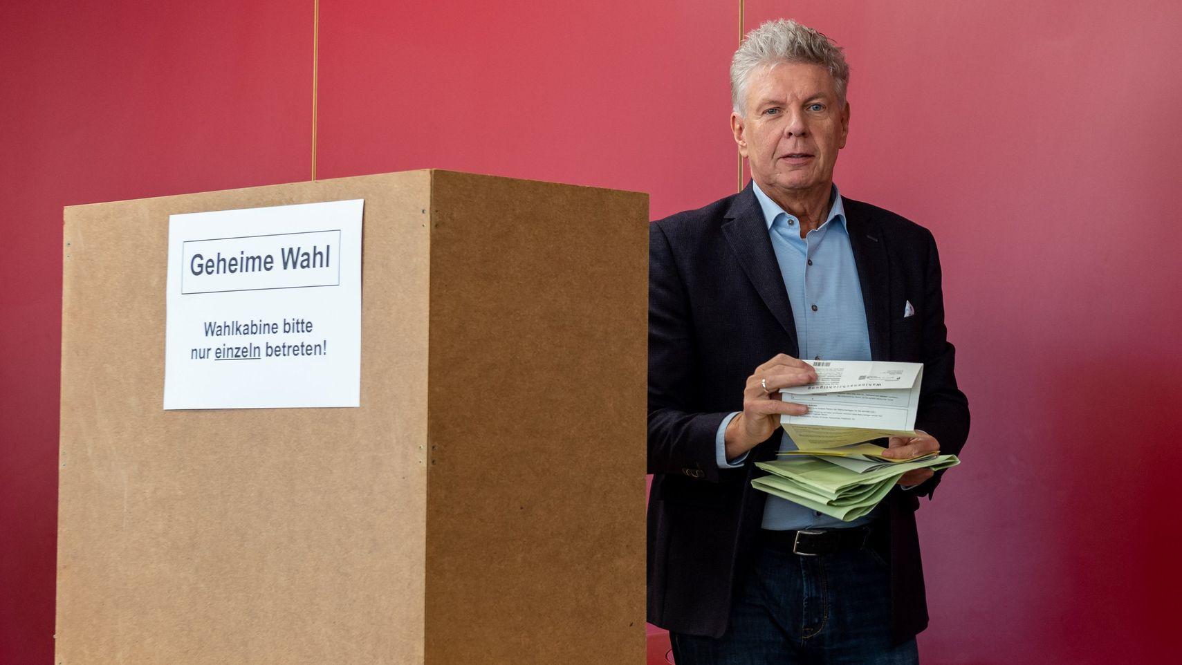 Oberbürgermeister Dieter Reiter verlässt mit seinen Wahlzetteln die Wahlkabine.