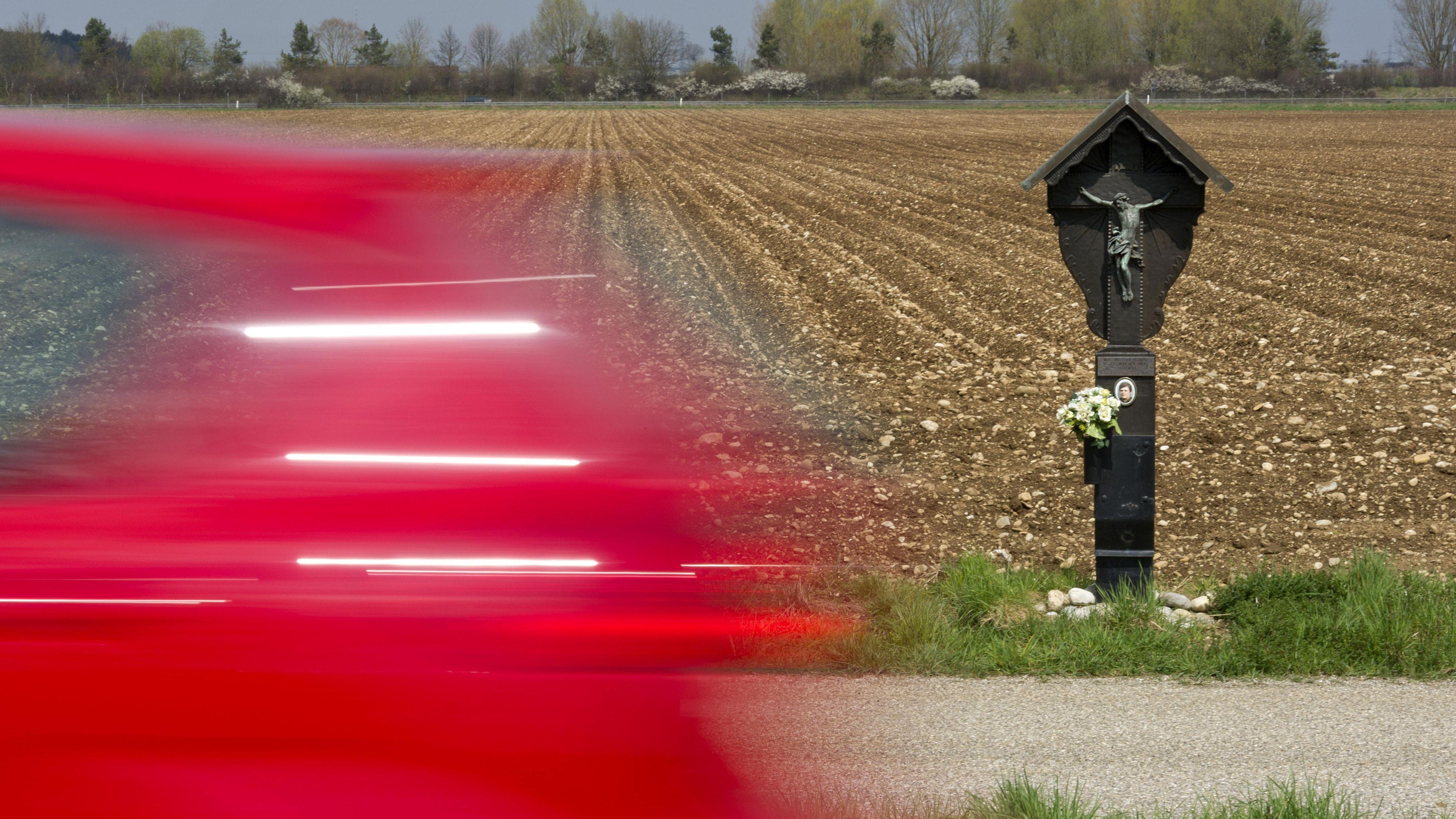 Symbolbild: Gedenkkreuz für ein Unfallopfer mit vorbeirasendem PKW an einer Landstraße in Oberbayern